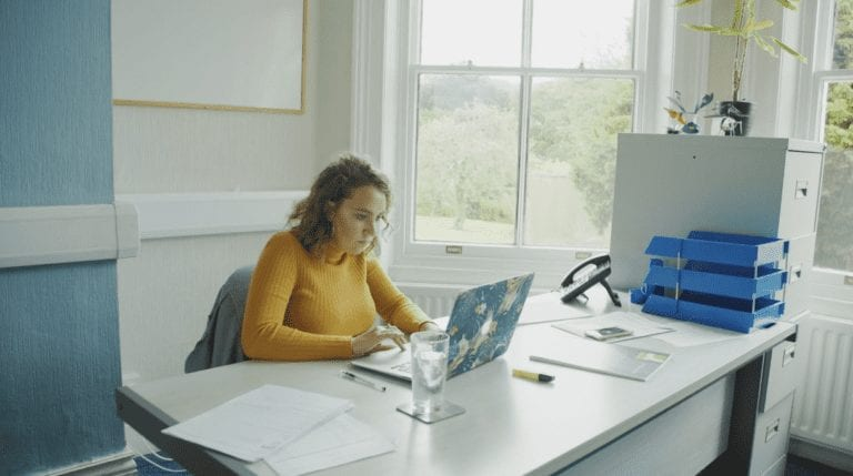 Photograph of Emma working at a desk in DTW office