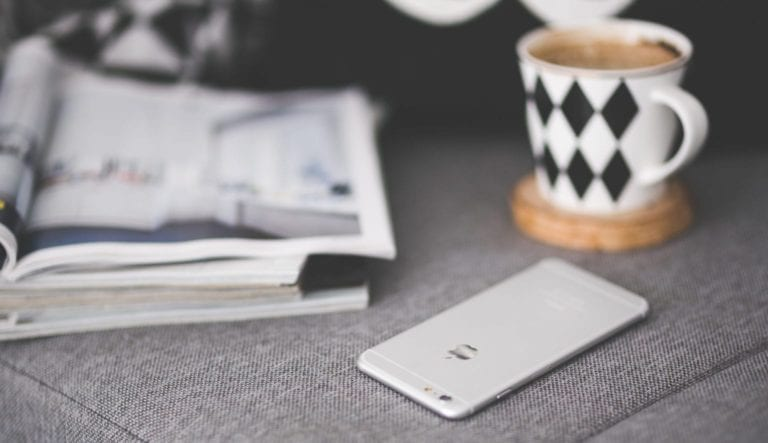 Close up photo of a phone on a grey couch with cup of coffee and book