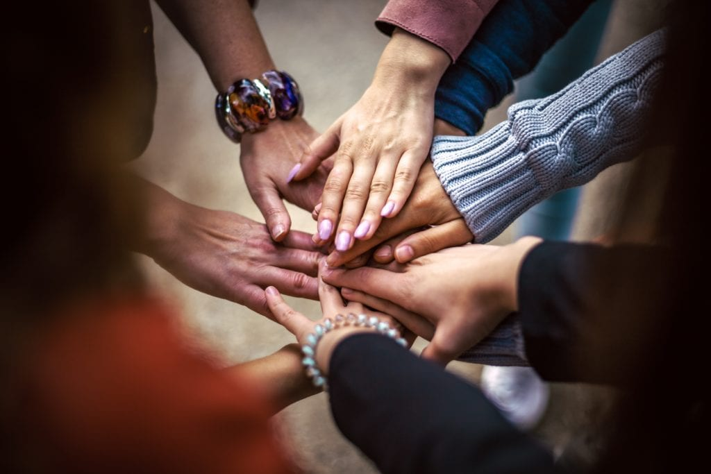 Photograph of many peoples hands all touching in centre point to form a team bond